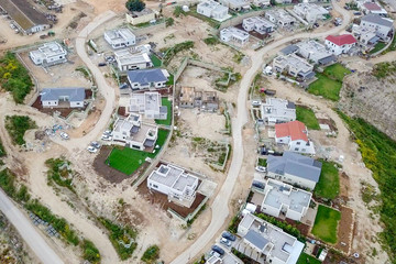 New Suburban houses at final Construction and development stages, Aerial image.