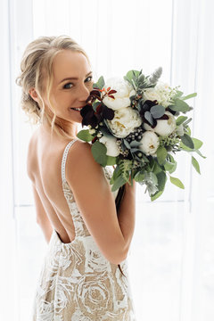 Very beautiful and happy bride holds her wedding bouquet of different blooming flowers and greenery