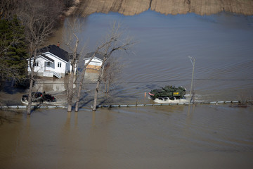 A Canadian Army Light Armoured Vehicle (LAV) is seen as it crosses a flooded road in Rigaud