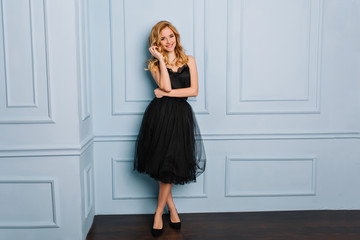 Full length portrait of beautiful young woman with wavy blonde hair, fashion model posing wearing stylish lace black dress and black shoues. Blue wall on background.