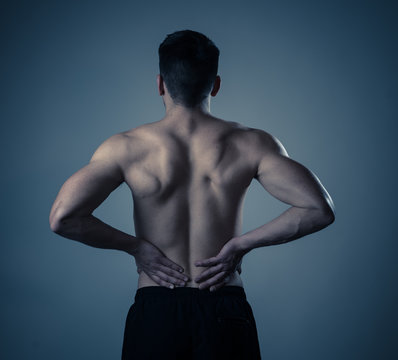 Strong young man suffering lower back pain in stress and bad posture