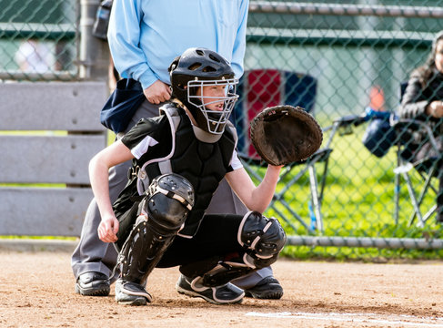 Female softball catcher in full protective gear ready to catch the first pitch.