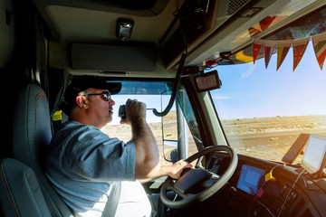 Male driver hands holding radio and steering wheel