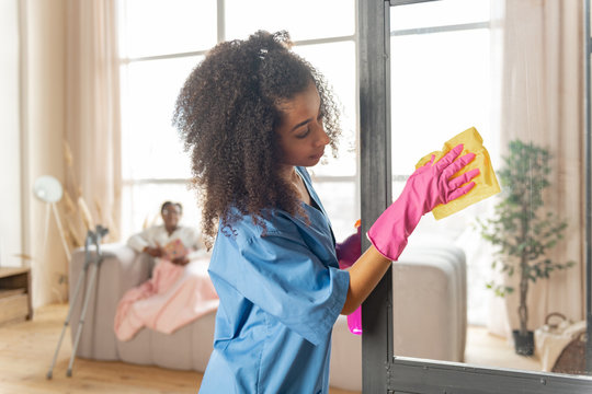Curly caregiver cleaning the glass door at home of patient