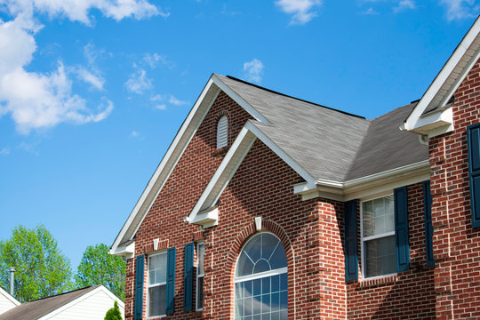 Residential Home with roofing gutters windows and blue sky
