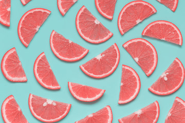 Creative summer pattern with grapefruit slices on pastel blue background. Minimal healthy food, color trend concept. Pop art style. Top view, flat lay.