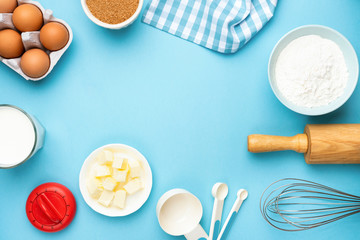 Baking utensils and ingredients on blue background. Eggs, butter, kitchen utensils, sugar, milk and flour. Recipe mock up, bakery background with copy space for text