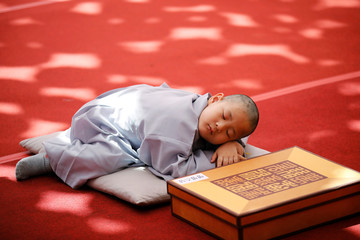 A novice monk naps after getting his head shaved by a Buddhist monk during an event to celebrate the upcoming Vesak Day, birthday of Buddha, at Jogye temple in Seoul