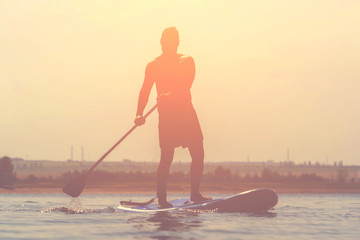 Sup surfing. Stand up paddle boarding. Surfer on sup board on the river.