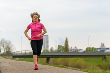 Middle age woman running outdoors