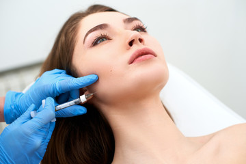 Beautician doctor with filler syringe making injection to jowls. Masseter lines reduction and face contouring therapy. Anti-aging treatment and face lift in cosmetology clinic. Patient lying on chair