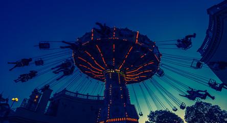 Photo sur Plexiglas Attraction parc spinning amusement park ride at sunset in vienna