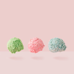 Ice cream scoops against pastel pink background. Minimal summer food concept.