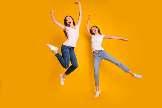 Full length body size view portrait of nice charming lovely attractive cheerful overjoyed slim fit thin straight-haired girls having fun isolated on bright vivid shine yellow background