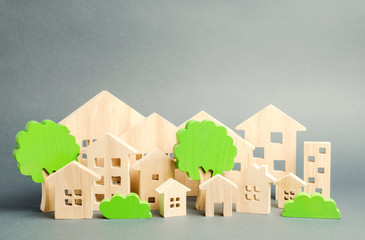 Miniature wooden toy houses and trees. Real estate concept. Architecture in the city. Infrastructure. Affordable housing. Construction of new buildings. City greening. Renovations and recovery