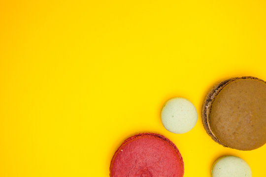 Top view of different flavors macroons over yellow background