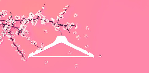 Creative fashion beauty concept. White wooden hanger hanging on the spring flowering branch on pink background. Spring sale concept discount store shopping empty hanger. Flat lay top view copy space. Wall mural