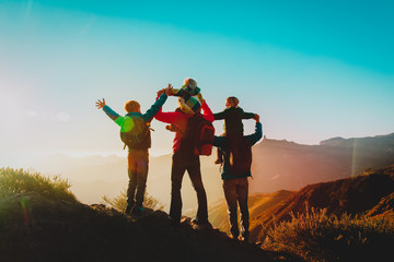happy family travel in mountains at sunset