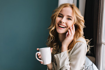 Young woman talking phone and laughing with cup of coffee, tea in hand, happy morning. She has beautiful wavy blonde hair. Room with blue, turquoise wall on background. Wearing nice lace pajama. Fototapete