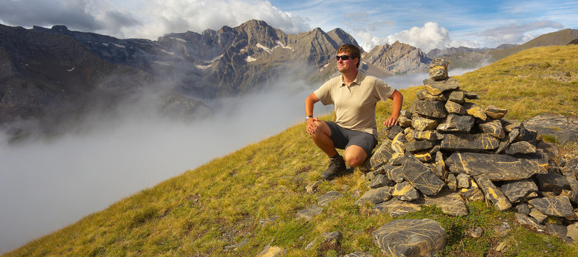 Pyrenees; mountain; tourist; resting; sitting; man; relax; relaxing; watching; deep; valley; hiking; outdoor; landscape; Occidentales; rocks; rocky; fog; France; highland; level; stones; stony; upland