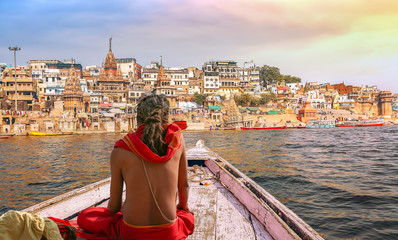 Varanasi city architecture with Ganges river bank at sunset with view of sadhu baba enjoying a boat ride on river Ganges. Wall mural