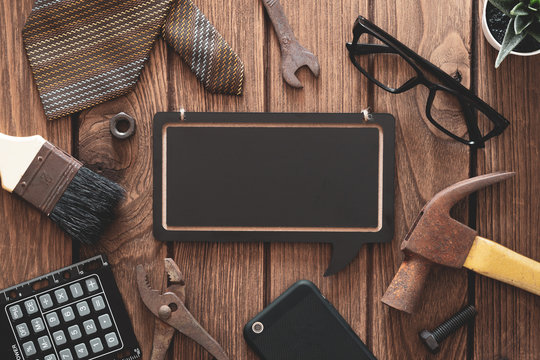 Labor Day and father's day background concept. Flat lay of construction blue collar handy tools and white collar's accessories over wooden background with black chalkboard.