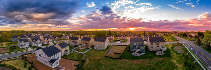 Aerial view of new construction street with luxury houses in a Maryland upper middle class neighborhood American real estate development in the USA with stunning sunset color sky