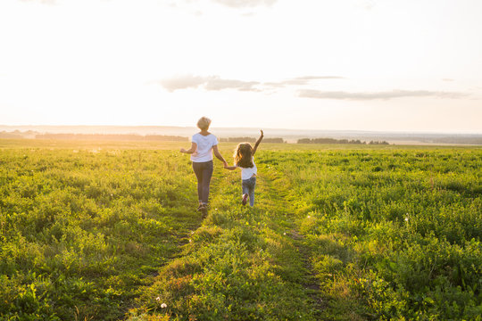 Rear view of mother and daughter running in green field with sunset on background