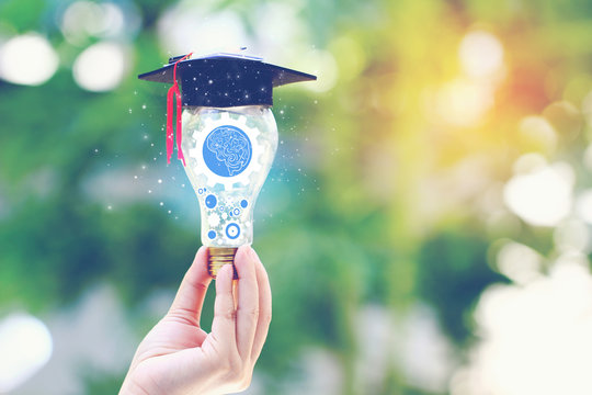 Woman hand holding cog inside in light bulb with graduates hat on natural green background, Education and Creative idea and innovation concept