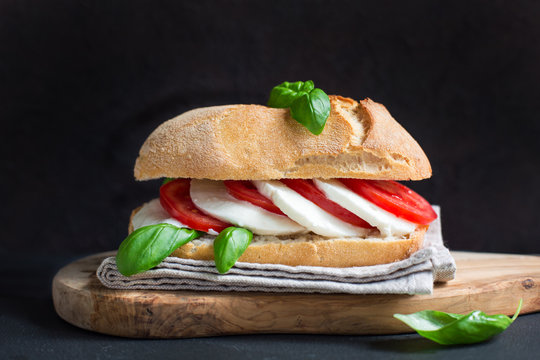 Caprese sandwich: Mozzarella, tomatoes, basil, italian bread, olive oil. Black background.