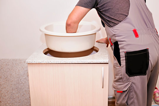 A handyman installing  kitchen artificial stone sink in a wooden cabinet covered with countertop using an electric jigsaw. Professional repair man service providing furniture install at home