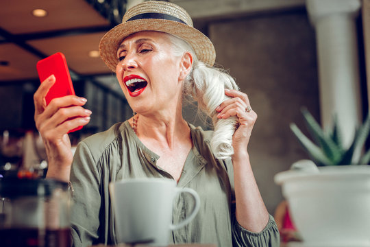 Joyful good looking woman taking beautiful selfies on her phone