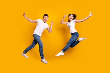 Full length side profile body size photo funky she her he him his pair jumping high yell scream shout fantastic mood show v-sign wear casual jeans denim white t-shirts isolated yellow background