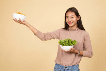 Young Asian woman with potato chips and salad.