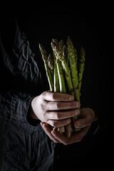 Bundle of raw organic green asparagus in dirty man's hand in black shirt.