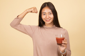 Strong healthy Asian woman with tomato juice.