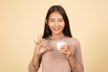 Healthy Asian woman drinking a glass of milk show OK sign.