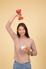 Healthy Asian woman drinking a glass of milk and dumbbell.