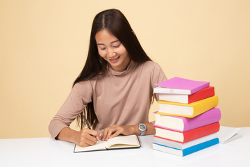 Young Asian woman read a book with books on table.