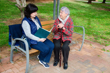 Older woman loves going for a walk with her female caregiver to the park and read books there.