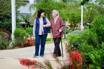 Cheerful female carer and an older woman with a walking stick stroll in a city park. Both are in a great mood.
