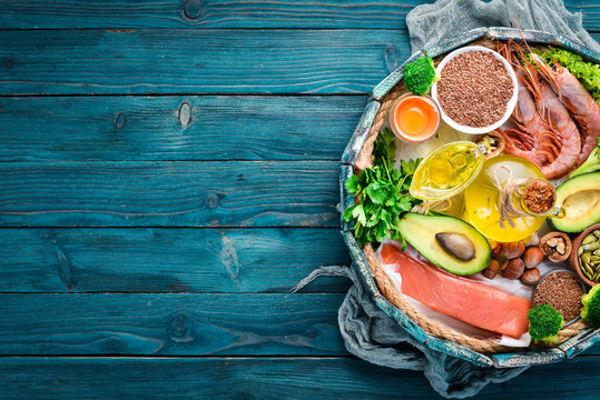 Balanced Keto diet. Healthy food: avocado, fish, shrimp, broccoli, flax, nuts, egg, parsley. Top view. Free space for your text.
