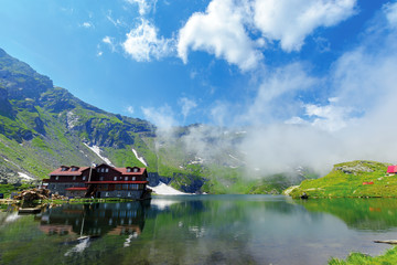 beautiful summer scenery around balea lake. grassy meadows and low clouds around. popular travel destination. location fagaras mountains, romania, europe. wonderful sunny weather