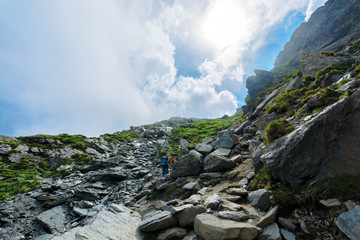 hiking uphill rocky slopes of fagaras mountains. hard path among big and sharp boulders. sunny summer weather with cloudy sky