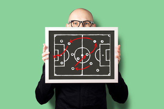 A man in a white shirt and jacket is holding a tablet with a drawn game tactics for football. Concept coach, tactics, sports betting and prediction.
