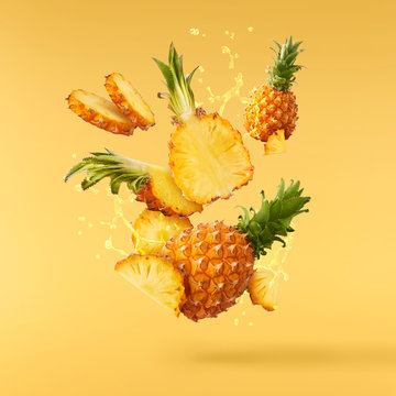 Flying in air fresh ripe whole and cut baby Pineapple with slices and leaves