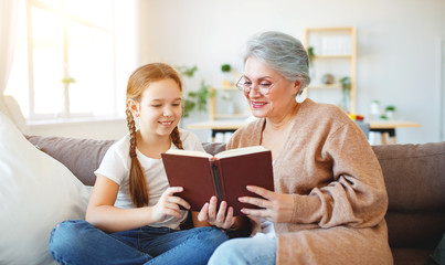 happy family grandmother reading to granddaughter book at home