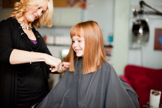 Happy Red-Haired Girl Getting Haircut in Hair Salon