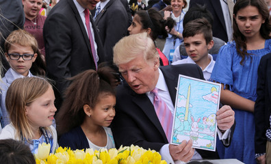 U.S. President Trump talks with child as he holds up colored in picture as he attends the 2019 White House Easter Egg Roll in Washington