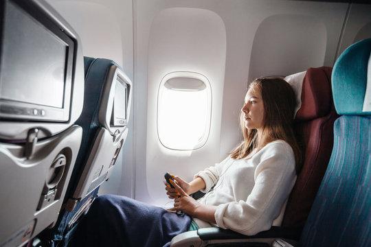 Teenage girl travelling by airplane
